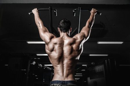 pull out: Handsome power athletic man on diet training pumping up back muscles pull up. Strong bodybuilder with six pack, perfect abs, back, shoulders, biceps, triceps and chest