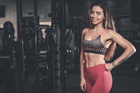physique: Sexy portrait model and a slim tanned womans body looking away in fitness gym