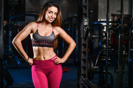 Sexy portrait model and a slim tanned womans body looking away in fitness gym