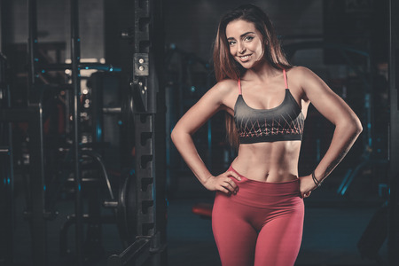 lose up: Sexy portrait model and a slim tanned womans body looking away in fitness gym