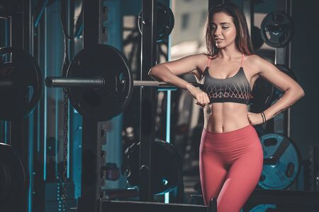 physique: Sexy pretty caucasian fitness model on diet resting and working out in the gym. Girl execute exercise with barbell Stock Photo