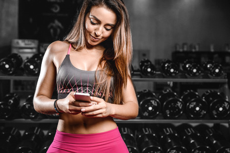 Pretty fitness girl with cellphone in gym.  Sexy young woman using gadget during workouts