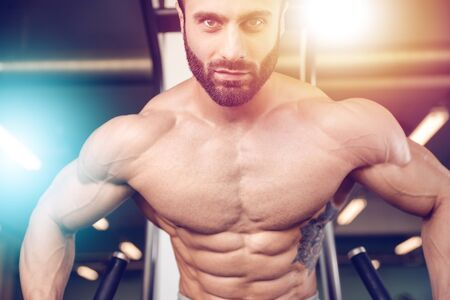 lose up: Handsome caucasian sexy fitness model in gym close up abs concept man on diet shirtless training six pack healthcare lifestyle crunch