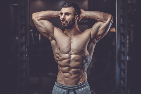 physique: Handsome caucasian sexy fitness model in gym close up abs concept man on diet shirtless training six pack healthcare lifestyle crunch
