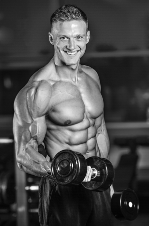 Handsome power athletic man on diet training pumping up muscles with dumbbell and barbell. Strong bodybuilder with six pack, perfect abs, shoulders, biceps, triceps and chest