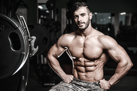 Handsome caucasian sexy fitness model in gym close up abs concept man on diet shirtless training six pack healthcare lifestyle crunch