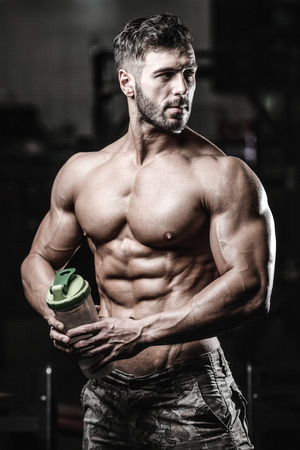 Muscular caucasian man on diet resting after exercise And drinking protein powder from shaker in the gym Stock Photo