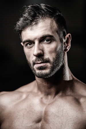 Portrait of a handsome guy on a background of gym. Face of brutal muscular sexy men in fitness gym