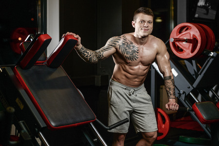 Strong and handsome athletic young tattoo man with muscles . Close-up of a power man on diet abs and biceps fitness and bodybuilding concept Stock Photo