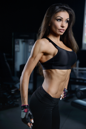 gaining: Beautiful sexy athletic young brunette Caucasian girl working out training in the gym gaining weight pumping up muscles and poses fitness and bodybuilding concept