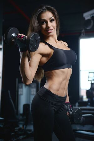 gaining: Beautiful sexy athletic young caucasian girl working out training arms in the gym gaining weight pumping up muscles bicep and tricep with dumbbells and on machines fitness and bodybuilding concept