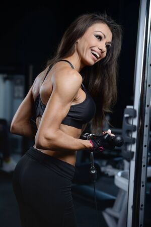 sixpack: Beautiful sexy athletic young caucasian girl working out training arms in the gym gaining weight pumping up muscles bicep and tricep with dumbbells and on machines fitness and bodybuilding concept
