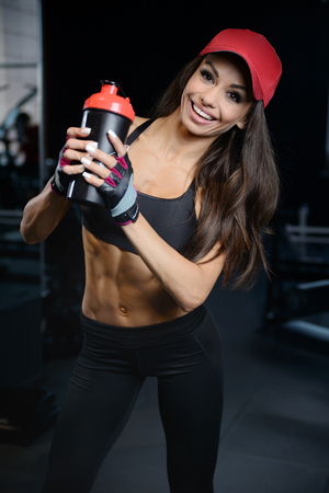 sixpack: Beautiful sexy athletic young brunette Caucasian girl taking protein sports nutrition in the gym and poses fitness and bodybuilding concept