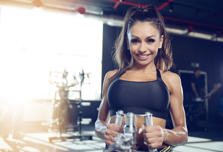 Beautiful sexy athletic young brunette Caucasian girl working out training pumping up back lats muscles in the gym gaining weight on machines posing fitness and bodybuilding concept Stock Photo