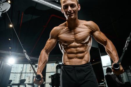Culturista caucásico guapo brutal que se resuelve en el pecho del entrenamiento del gimnasio que bombea los músculos pectorales withdumbbells y en los cruces que ganan el peso y plantea concepto de la aptitud y del levantamiento de pesas Foto de archivo - 87258016