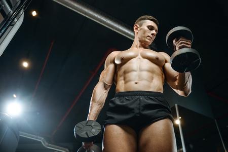 Knappe gespierde blanke man van model uiterlijk trainen van de armen in de sportschool verkrijgen van gewicht oppompen spieren biceps en triceps met halters en op machines fitness en bodybuilding concept