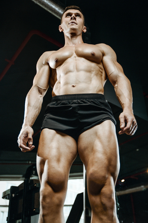 muscle gain: Handsome young muscular Caucasian man of model appearance working out in the gym training legs quadriceps and hamstrings on machines and with a barbell pumping up fitness and bodybuilding concept Stock Photo
