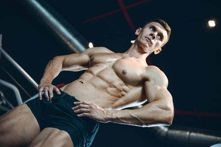 muscle gain: Handsome young muscular Caucasian man of model appearance working out training in the gym gaining weight pumping up muscles and poses fitness and bodybuilding concept Stock Photo