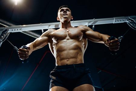 Culturista caucásico guapo brutal que se resuelve en el pecho del entrenamiento del gimnasio que bombea los músculos pectorales withdumbbells y en los cruces que ganan el peso y plantea concepto de la aptitud y del levantamiento de pesas Foto de archivo - 88057463