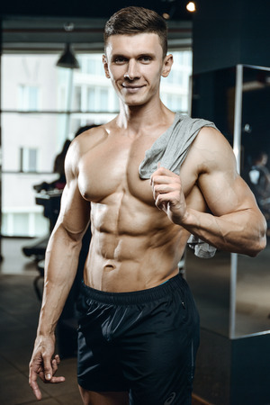 Handsome young muscular Caucasian man of model appearance working out training in the gym gaining weight pumping up muscles and poses fitness and bodybuilding concept Standard-Bild - 87943636