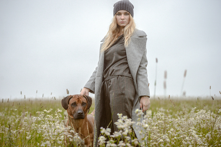 perros vestidos: cute well dressed pretty young caucasian blonde hair adult teenage girl in fashion dress coat outdoor with a dog at mist countryside landscape field spring or autumn weather depressed mood Foto de archivo