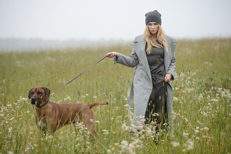 cute well dressed pretty young caucasian blonde hair adult teenage girl in fashion dress coat outdoor with a dog at mist countryside landscape field spring or autumn weather depressed mood Stock Photo
