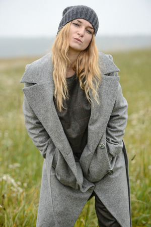 cute well dressed pretty young caucasian blonde hair adult teenage girl in fashion dress coat outdoor near farm house at mist countryside landscape field spring or autumn weather depressed mood