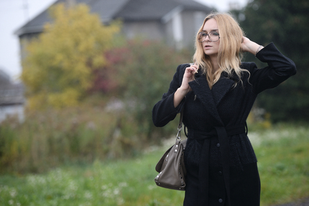 cute well dressed pretty young caucasian blonde hair adult teenage girl in fashion dress coat outdoor near road and house mist countryside landscape field spring or autumn weather depressed mood