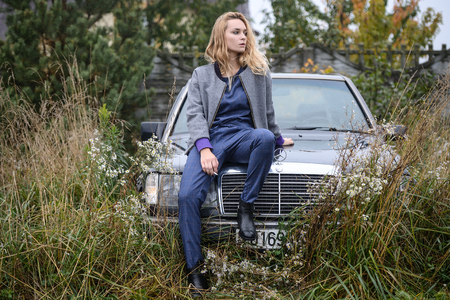 sexy cute well dressed pretty young caucasian blonde hair adult teenage girl in fashion dress near car smoking cigarette at countryside landscape spring or autumn weather depressed mood
