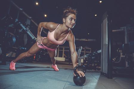 """Menina """"sexy"""" atlética nova caucasiano atlética que elabora na caixa do treinamento da ginástica que bombeia acima os músculos peitorais com dumbbells e em crossovers que ganham o peso e o conceito da aptidão e do bodybuilding das poses Foto de archivo - 88996562"""
