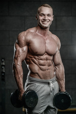 muscle gain: Handsome young muscular Caucasian man of model appearance working out training pumping up abdominal muscles abs sixpacks in the gym gaining weight and poses fitness and bodybuilding concept