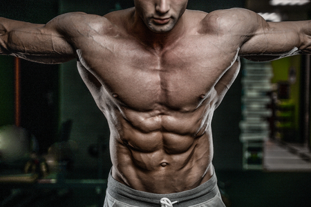 Handsome young muscular Caucasian man of model appearance working out training pumping up abdominal muscles abs sixpacks in the gym gaining weight and poses fitness and bodybuilding concept