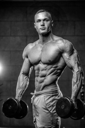 muscle gain: Attractive young muscular sexy Caucasian man of model appearance working out training in the gym gaining weight pumping up muscles and poses fitness and bodybuilding concept