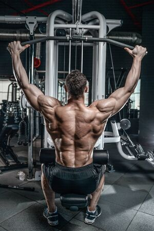 muscle gain: Handsome young muscular Caucasian man of model appearance working out training pumping up back lats muscles in the gym gaining weight on machines posing fitness and bodybuilding concept