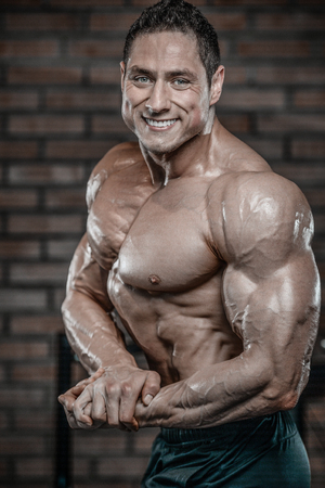 muscle gain: Brutal handsome Caucasian bodybuilder working out training in the gym gaining weight pumping up muscles and poses fitness and bodybuilding concept