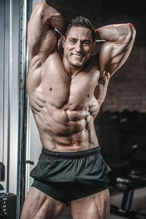 Hübscher junger muskulöser kaukasischer Mann des Modellauftrittes das Training ausbildend, das oben Bauchmuskeln-ABS sixpacks in der zunehmenden Gewichtszunahme der Turnhalle pumpt und Eignung und Bodybuildingkonzept wirft Standard-Bild - 89208755