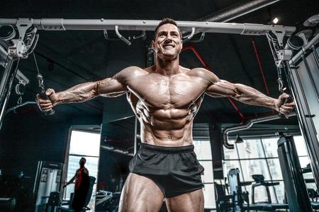 Culturista caucásico guapo brutal que se resuelve en el pecho del entrenamiento del gimnasio que bombea los músculos pectorales withdumbbells y en los cruces que ganan el peso y plantea concepto de la aptitud y del levantamiento de pesas