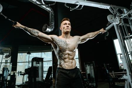 Brutal belo fisiculturista caucasiano trabalhando no ginásio treinando peito pulando músculos peitorais com dumbbells e crossovers ganhando peso e coloca conceito de fitness e musculação Foto de archivo - 89435265