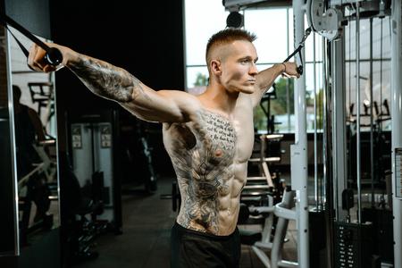 Culturista caucásico guapo brutal que se resuelve en el pecho del entrenamiento del gimnasio que bombea los músculos pectorales withdumbbells y en los cruces que ganan el peso y plantea concepto de la aptitud y del levantamiento de pesas Foto de archivo - 89678465