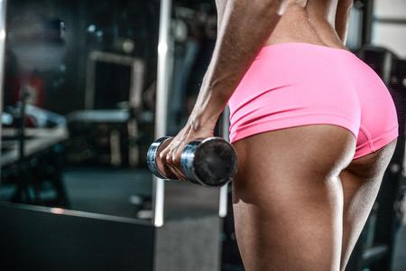 Mooi sexy atletisch jong donkerbruin Kaukasisch meisje die tonend goed rond gemaakt uiteinde glutes de dichte geschiktheid van de billenas en het bodybuilding concept stellen