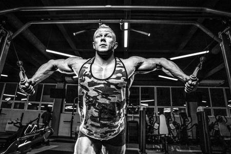 Brutal bonito fisiculturista caucasiana, exercitando-se no peito de treinamento de ginásio bombeamento músculos peitorais withdumbbells e em crossovers ganhando peso e poses Foto de archivo - 90090200