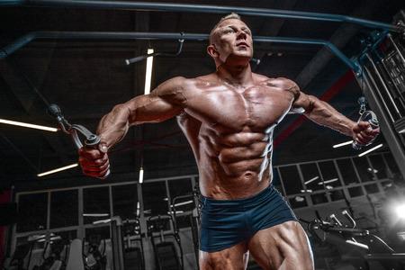 Culturista caucásico guapo brutal que se resuelve en el pecho del entrenamiento del gimnasio que bombea los músculos pectorales withdumbbells y en los cruces que ganan el peso y plantea concepto de la aptitud y del levantamiento de pesas Foto de archivo - 89994518