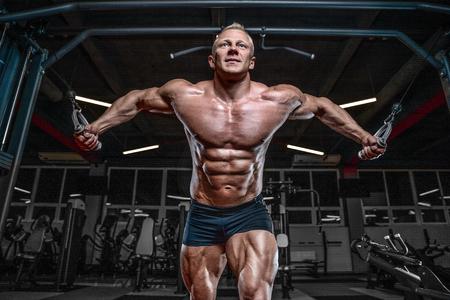 Brutal belo fisiculturista caucasiano trabalhando no ginásio treinando peito pulando músculos peitorais com dumbbells e crossovers ganhando peso e coloca conceito de fitness e musculação Foto de archivo - 90090221