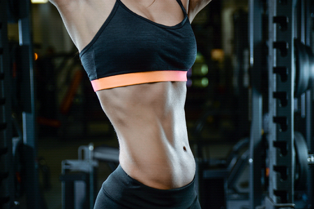 Beautiful sexy athletic young brunette Caucasian girl working out training pumping up abdominal muscles abs sixpacks in the gym on machines gaining weight and poses fitness and bodybuilding concept Stock Photo