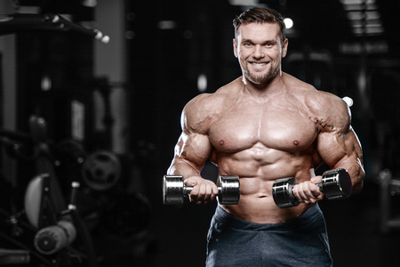 Brutal sexy strong bodybuilder athletic fitness man pumping up abs muscles workout bodybuilding concept background - muscular handsome men doing health care fitness exercises in gym naked torso