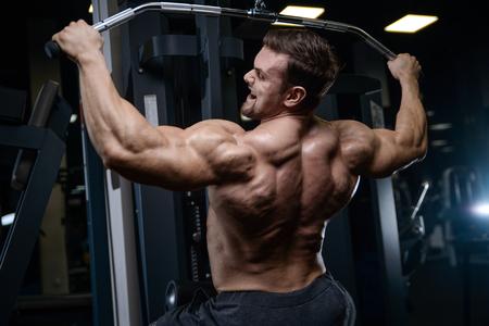 Brutalny silny kulturysta lekkoatletyczny mężczyzna pompowanie mięśni abs trening kulturystyka koncepcja tło - muskularni przystojni mężczyźni robią ćwiczenia zdrowotne fitness w tułowiu siłowni