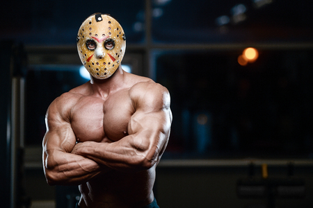 horror brutal Jason mask man strong bodybuilder athletic fitness man in scary hockey mask in the gym fight warrior in Friday 13th pumping up muscles workout bodybuilding concept background