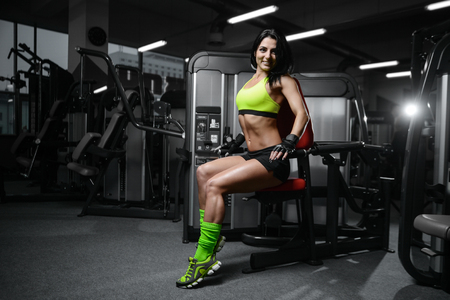 Beautiful brunette sexy athletic muscular young brunette Caucasian fitness girl working out training in the gym gaining weight pumping up abs muscles and poses bodybuilding health care concept