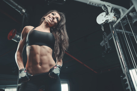 Beautiful sexy athletic young brunette Caucasian girl working out training pumping up abdominal muscles abs sixpacks in the gym on machines gaining weight and poses