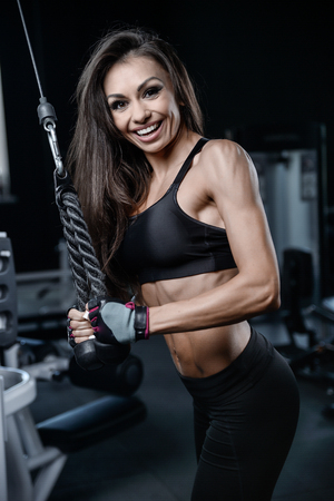 Beautiful sexy athletic young caucasian girl working out training arms in the gym gaining weight pumping up muscles bicep and tricep with dumbbells and on machines fitness and bodybuilding concept